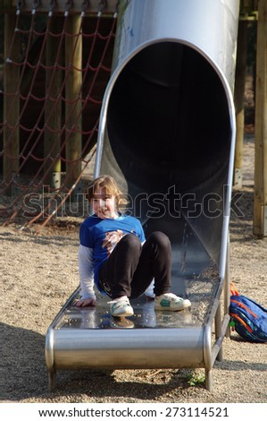 Portrait of cute girl on slide - stock photo