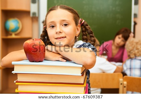 Portrait of cute girl on top of book stack looking at camera - stock photo
