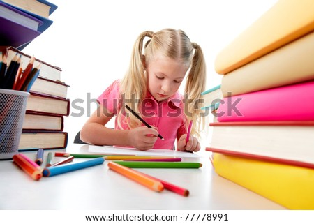 Portrait of cute girl sitting among stacks of literature and drawing