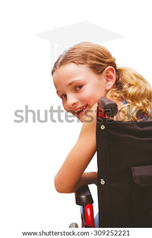 Portrait of cute girl sitting in wheelchair against silhouette of graduate - stock photo