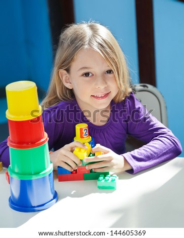 Portrait of cute girl sitting with toys at desk in preschool - stock photo