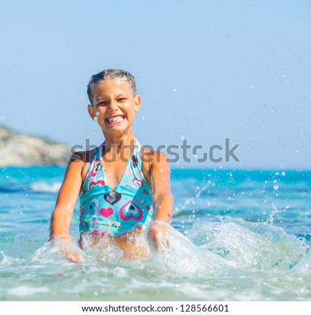 Portrait of cute girl swimming and squirting in the transparent sea - stock photo