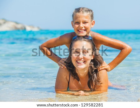 Portrait of cute girl swimming with her mother in the transparent sea - stock photo