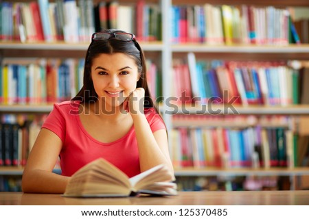 Portrait of cute girl with open book looking at camera in college library - stock photo