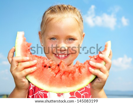 Portrait of cute girl with peace of red watermelon on blue sky background - stock photo