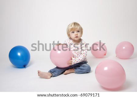 Portrait of cute girl with pink and blue balloons having fun at the party - stock photo