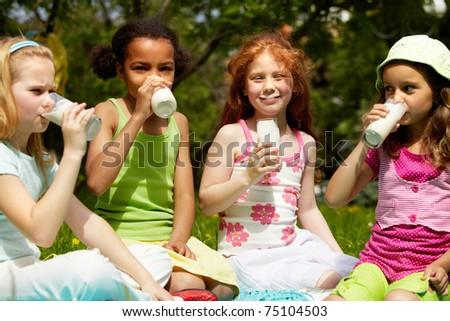 Portrait of cute girls drinking kefir outdoors - stock photo
