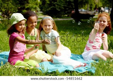 Portrait of cute girls having fun on grass in park - stock photo