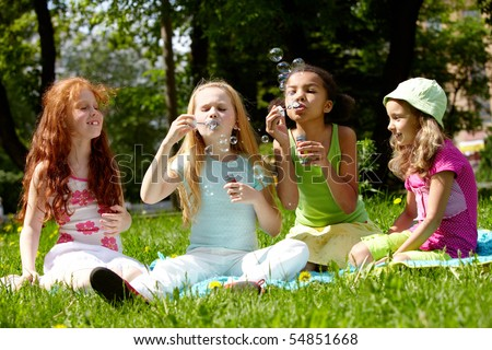 Portrait of cute girls playing on green lawn in park - stock photo