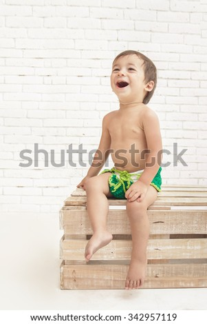 portrait of cute handsome toddler laughing while sitting on wooden box - stock photo
