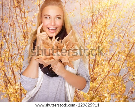 Portrait of cute happy girl with dry maple leaves bouquet in the park, spending time outdoors, enjoying autumn concept - stock photo