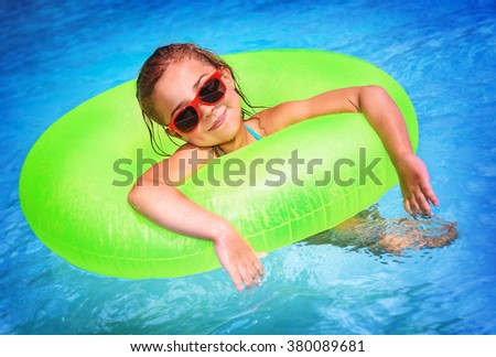 Portrait of cute happy little girl having fun in swimming pool, floating in blue refreshing water with big green rubber ring, active summer vacation on the beach - stock photo