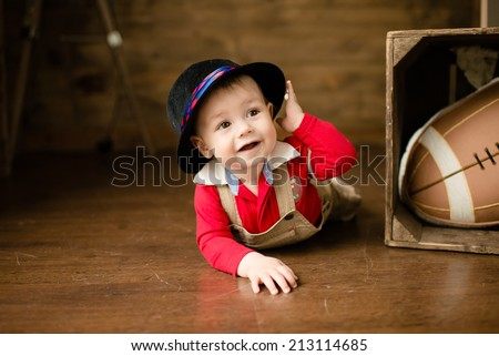 Portrait of cute happy 8 month old baby boy with funny hat. Photo of funny babe. - stock photo