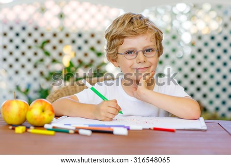 Portrait of cute happy preschool kid boy with glasses at home making homework. Little child painting with colorful pencils, indoors. School, education concept - stock photo