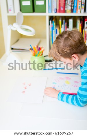 Portrait of cute happy schoolkid at home drawing