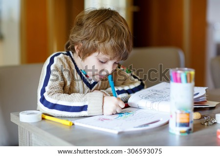 Portrait of cute happy schoolkid at home making homework. Little child painting with colorful pencils, indoors. - stock photo