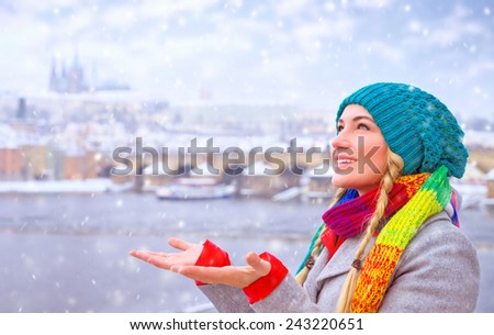 Portrait of cute happy woman enjoy snowfall in beautiful Prague city, catches snowflakes by hands with pleasure, enjoying winter holidays