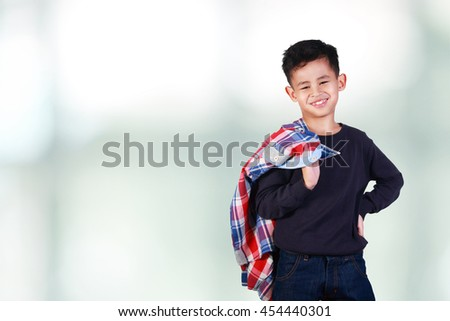 Portrait of cute happy young Asian boy smiling and holding jacket on his shoulder - stock photo