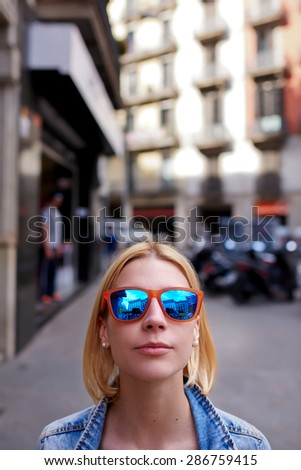 Portrait of cute hipster girl in summer sunglasses looking to the camera with copy space above her head, stylish and tend female in urban setting looking to you, youth lifestyle - stock photo