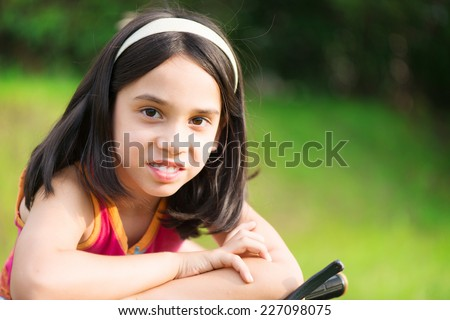 Portrait of cute hispanic girl on bicycle - stock photo