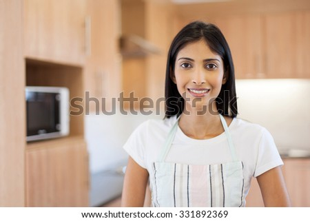 portrait of cute indian woman in kitchen with apron - stock photo