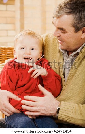 Portrait of cute kid having fun with his grandfather near by - stock photo