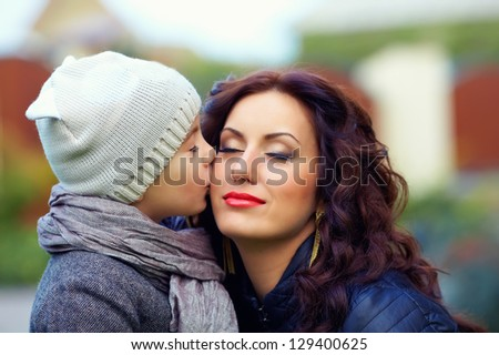 portrait of cute kid kissing mother - stock photo