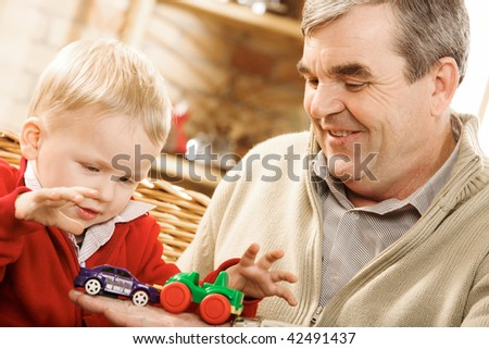 Portrait of cute kid looking at toy car on his grandfather hand - stock photo