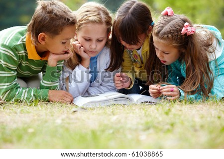 Portrait of cute kids reading book in natural environment together - stock photo