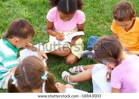 Portrait of cute kids seated on green grass with copybooks and pencils - stock photo