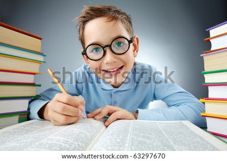Portrait of cute lad in eyeglasses making notes in book during reading - stock photo