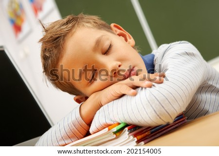 Portrait of cute lad sleeping with his head on copybooks in classroom - stock photo
