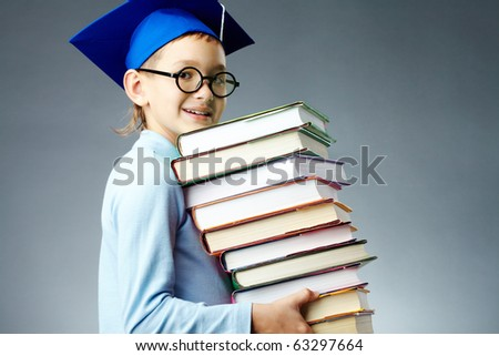 Portrait of cute lad with stack of books looking at camera - stock photo