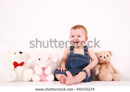 Portrait of cute laughing baby with plush toys - stock photo