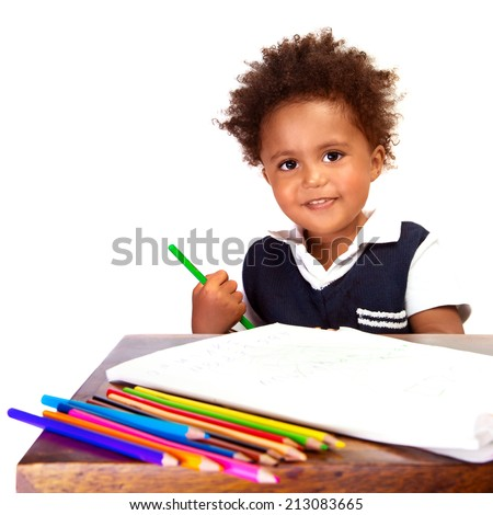 Portrait of cute little African American schoolboy sitting behind the desk and drawing, happy pupil isolated on white background, back to school concept  - stock photo