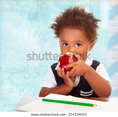 Portrait of cute little African boy sit behind a desk and biting big red apple, drawing using green pencil, having lunch in classroom, happy preschooler concept - stock photo