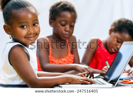 Portrait of cute little African girl doing homework on computer with friends at desk.Isolated on light background. - stock photo