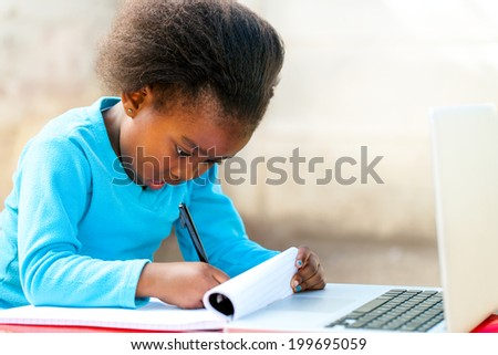 Portrait of cute little African student doing schoolwork outdoors.