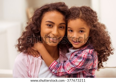 Portrait of cute little Afro-American girl and her beautiful young mother hugging, looking in camera and smiling. - stock photo