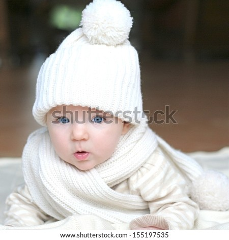 Portrait of cute little baby with big beautiful blue eyes laying on blanket wearing cozy warm white knitted hat and scarf - stock photo