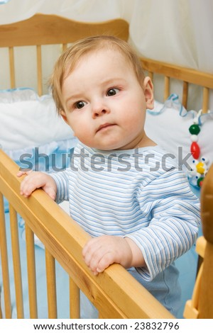 Portrait of cute little boy in his crib - stock photo