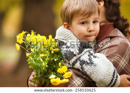 Portrait of cute little boy in his mother's arms. Child is tired of walking, so mammy is carrying her son, together with a bouquet of flowers. - stock photo
