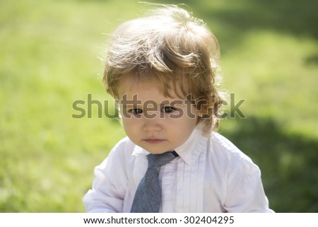 Portrait of cute little boy kid with blond curly hair and round cheeks in white shirt with necktie standing on green grass yard looking away sunny day outdoor on natural background, horizontal photo - stock photo