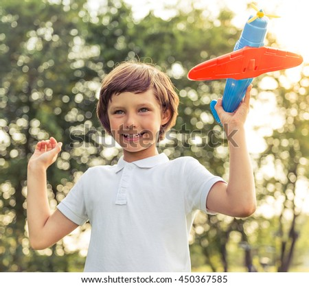 Portrait of cute little boy looking forward and smiling while playing with a toy airplane in the park - stock photo