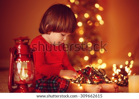 Portrait of cute little boy playing with Christmas light at home, with copy space - stock photo
