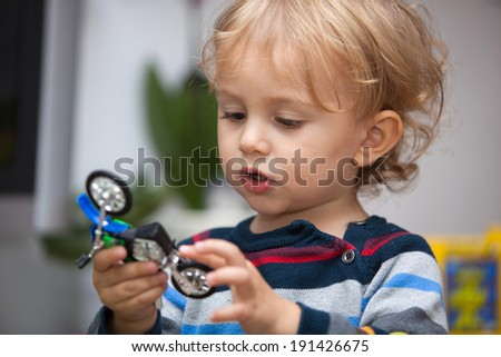 Portrait of cute little boy playing with motorcycle toy.