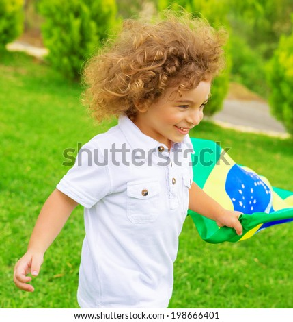 Portrait of cute little boy running with Brazil national flag, cheerful young football player, fan of Brazilian football team - stock photo