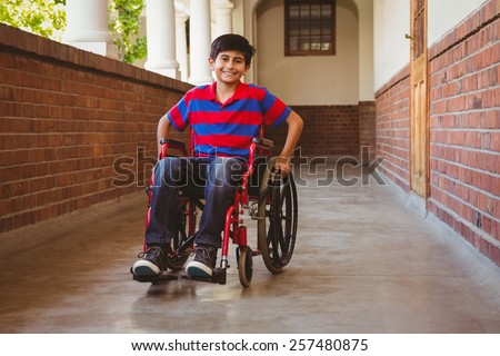 Portrait of cute little boy sitting in wheelchair in school corridor - stock photo
