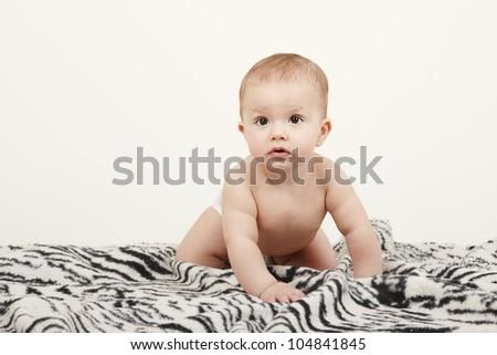Portrait of cute little boy sitting on blanket - stock photo