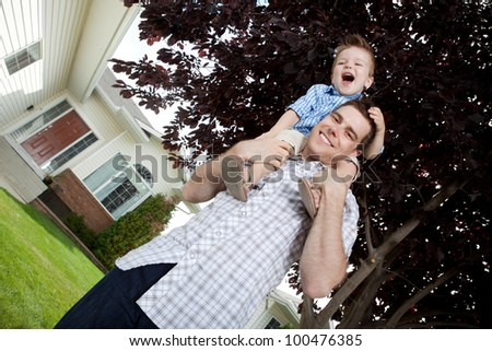 Portrait Of Cute Little Boy Sitting On Father's Shoulder.